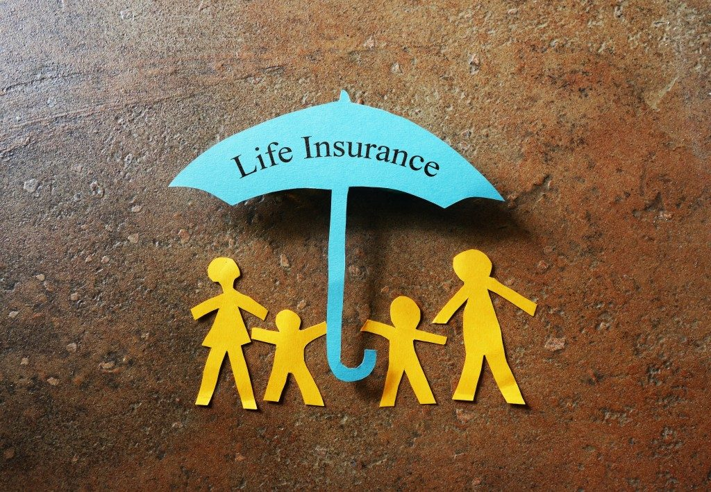 Paper family of four under a Life Insurance paper cutout umbrella