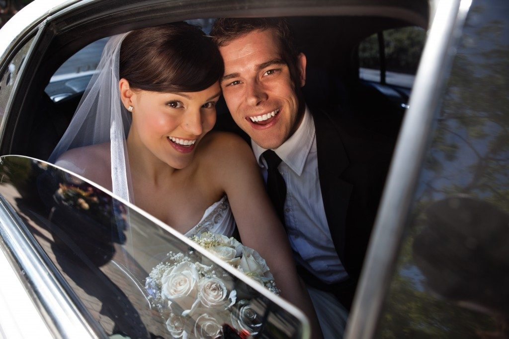 Portrait of happy newly wed couple in car