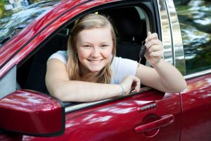 blond teenage girl sitting in her new car