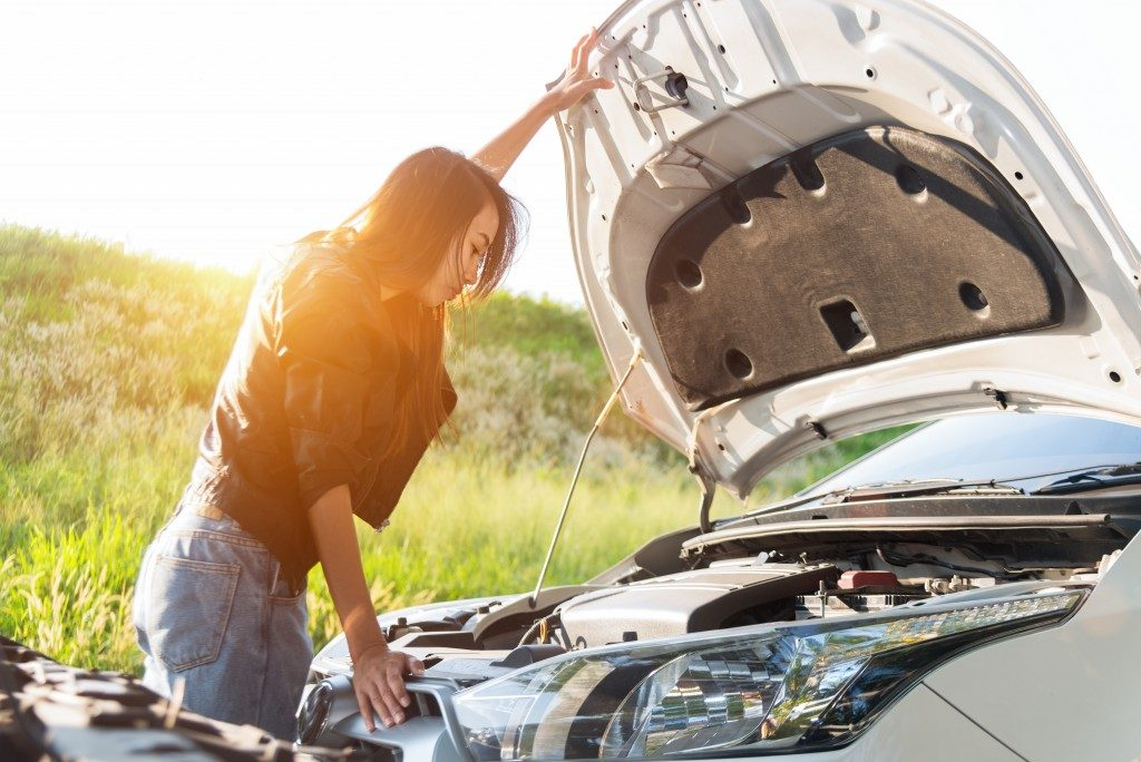 girl checking her car's engine